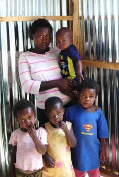 Suzan and her children inside her new shack