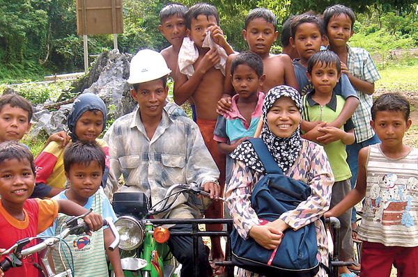 Tri Mumpuni Iskandar (front row, second from r., with villagers in Aceh, Indonesia) developed microh