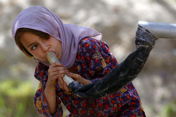 An Afghan girl drinks water from a well through a makeshift faucet in a village in Kandahar Province