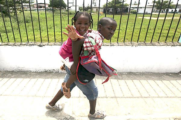 A boy carries his sister along a street after classes in Bata, Equatorial Guinea, in west central Af