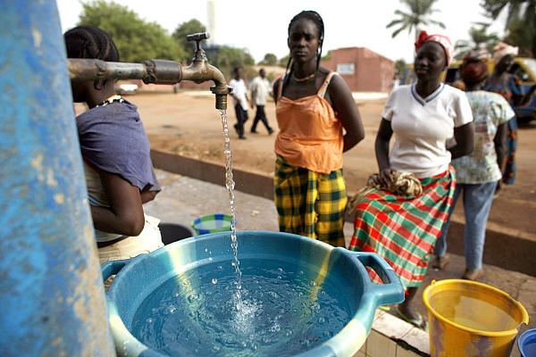 Girls fill plastic basins at a free water tap operated by a charity in a neighborhood of Bissau, Gui