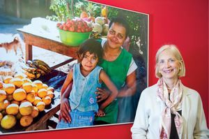 Pro Mujer cofounder Lynne Patterson stands next to a photo mural in the Latin American microlender's New York headquarters.