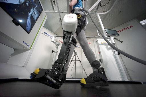 A model demonstrates the Welwalk WW-1000, a wearable robotic leg brace designed to help partially paralyzed people walk