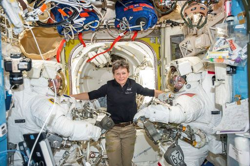 Astronaut Peggy Whitson, center, floats inside the Quest airlock of the International Space Station