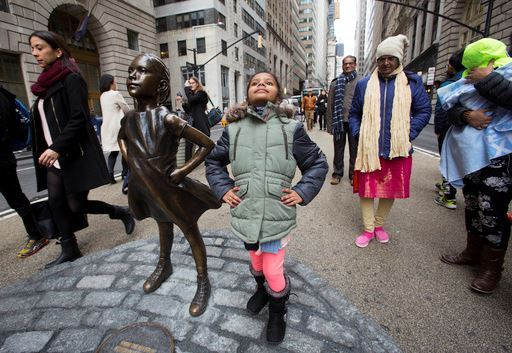 "Shriya Gupta of Cherokee, N.C. strikes a pose with a statue titled ""Fearless Girl"", Wednesday, March 8, 2017, in New York."