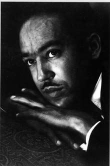 Black and white photo of Langston Hughes looking upward, resting his head on his hand.