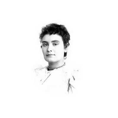 Head and shoulders portrait of Anne Sullivan. In this image, Anne faces the viewer with a slight smile.  Her light-colored dress has a high neck and she wears a necklace.