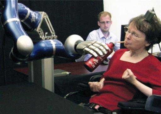 In this April 12, 2011 image from video provided by braingate2.org, Cathy Hutchinson of East Taunton, Mass. sips a drink held by a robotic arm during a test at a long-term care residence for adults with neurological disease in Dorchester, Mass. A report by researchers published in the Thursday, May 17, 2012 issue of the journal Nature describes how two people, paralyzed years before by strokes, were able to control free-standing robotic arms with the help of a tiny sensor planted in their brains. The sensor, about the size of a baby aspirin, eavesdropped on the electrical activity of a few dozen brain cells as the people imagined moving their arms. It then sent signals to a computer, which translated them into commands for the robot arms. (AP Photo/braingate2.org)