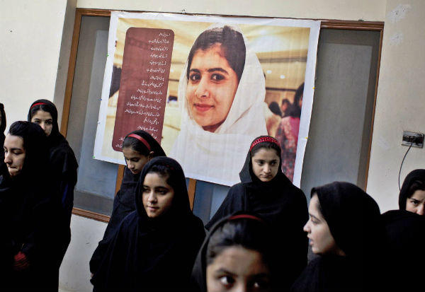Pakistani girls gather under a poster of Malala Yousufzai in her old school in Mingora, Swat Valley, Pakistan. <P>(Anja Niedringhaus/AP)