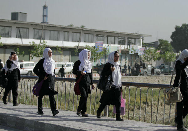 Afghan school girls walk near the entrance gate of the presidential palace after an attack by the Taliban in Kabul, Afghanistan, Tuesday, June 25. <P>(Ahmad Jamshid/AP)