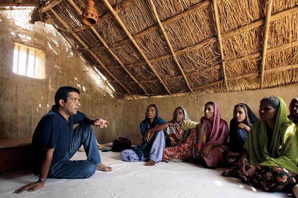 Anshu Gupta (l.), founding director of GOONJ, speaks to women in Rupaspur, a rural village in northeast India.  <P>Manan Vatsyayana/AFP/Getty Images/file