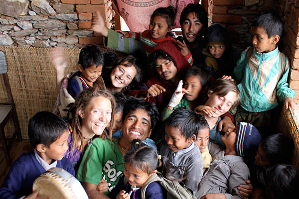 Surya Karki (c., green T-shirt), cofounders, and volunteers at Maya Universe Academy in Tanahun, Nepal, huddle with children enrolled at their school. <P> Joseph D. Layden/Maya Universe Academy