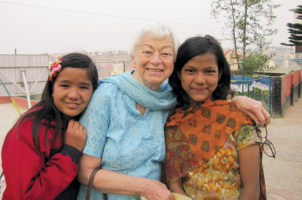 Olga Murray poses with two of the many girls she has helped through the Nepal Youth Foundation, which she founded in 1990.