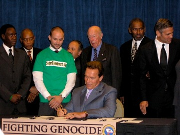 California Governor Schwarzenegger  signing the bill into law, with Sterling, Clooney, and Cheadle present.
