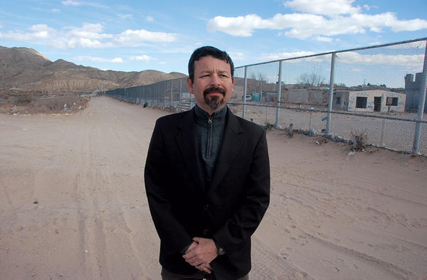 Fernando Garcia, director of the Border Network for Human Rights in El Paso, Texas, stands in front of the US-Mexican border fence.  <P>Tom A. Peter