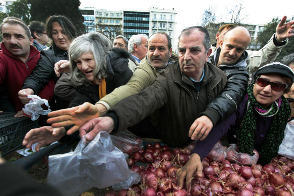 Greeks wait to receive free onions and other vegetables offered by farmers in Syntagma Square in Athens last January. In the US, many organizations work to share leftover fruits and vegetables with those in need, based on the ancient idea known as gleaning.  <P>Yannis Behrakis/Reuters/File