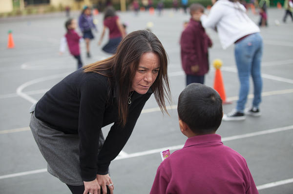 Jennifer Epps, principal of Synergy Charter Academy in Los Angeles, talks to a student about his homework on the playground.  <P>Stephanie Diani/Special to The Christian Science Monitor