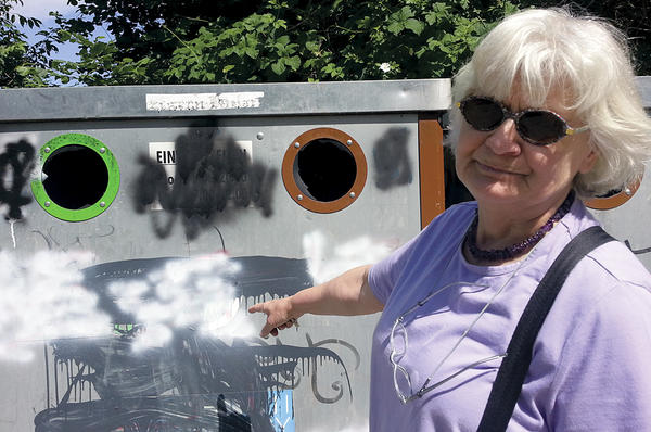 Irmela Mensah-Schramm points to a garbage bin that had been decorated with Nazi symbols before she painted over them in Zossen, Germany. <P> Isabelle de Pommereau