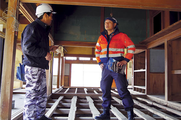 Seiji Yoshimura (r.), who responds to disasters throughout Asia, talks to carpenter Kenji Hoshino at a tsunami-struck house in Ishinomaki, Japan. <P> Takehiko Kambayashi