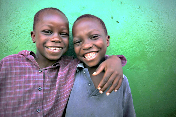 Two boys laugh as they pose for a photo in a neighborhood of Monrovia, Liberia. Aids groups such as Oxfam would like to portray the people they help as trustworthy partners capable of helping themselves, and not as victims. But publicity campaigns that show a suffering 'poster child' remain more effective in eliciting donations.  <P>Thierry Gouegnon/Reuters