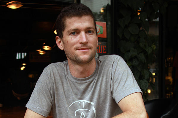 Colorado native Colin Flahive sits at the bar of Salvador's Coffee House in Kunming, the capital of China's southwestern Yunnan Province. Employing young women from rural areas led him to take a number of steps to help his employees and the community.  <P>Michael Ives