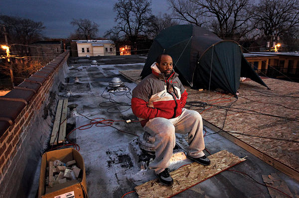 Pastor Corey Brooks sits on the roof of an abandoned motel where he camped out across the street from his New Beginnings Church in Chicago. <P>Brian Cassella/Chicago Tribune/Getty Images