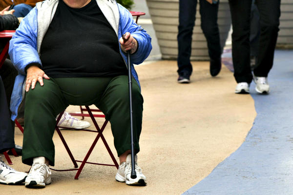 An overweight woman sits on a chair in Times Square in New York. The startup 'Halfsies' aims to cut obesity and increase food aid to the hungry by serving diners half a portion and donating the cost of the rest of the meal to charity. <P>Lucas Jackson/Reuters