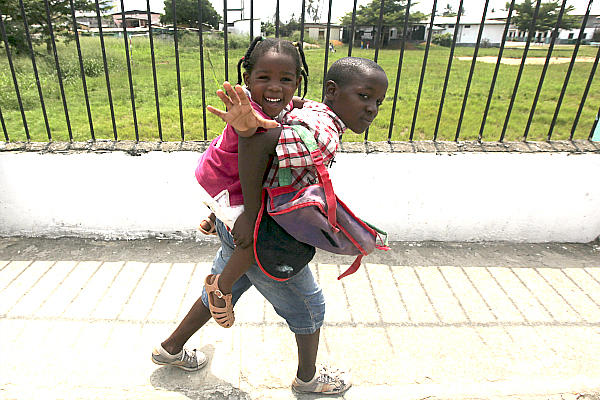A boy carries his sister along a street after classes in Bata, Equatorial Guinea, in west central Africa earlier this month. Serving others causes a mental shift from 'me' to 'we,' the author says.  <P>Amr Abdallah Dalsh/Reuters