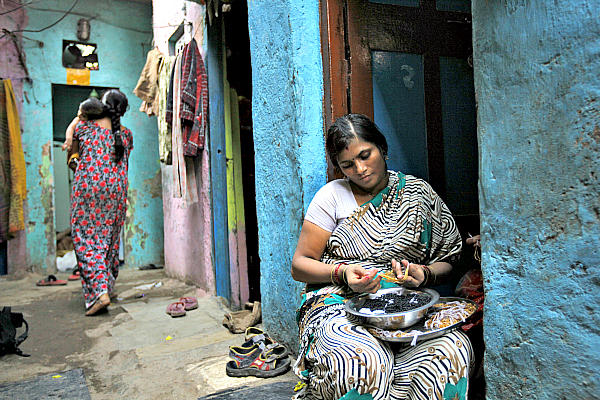 Shobha Vakade, who took a loan of rupees 18,000 ($400) from a microfinance company to start her own business, strings beads into necklaces outside her house in a slum in Mumbai, India. Microloan groups are expanding to include other services to clients, including savings accounts and health and education services.  <P>Danish Siddiqui/Reuters/File