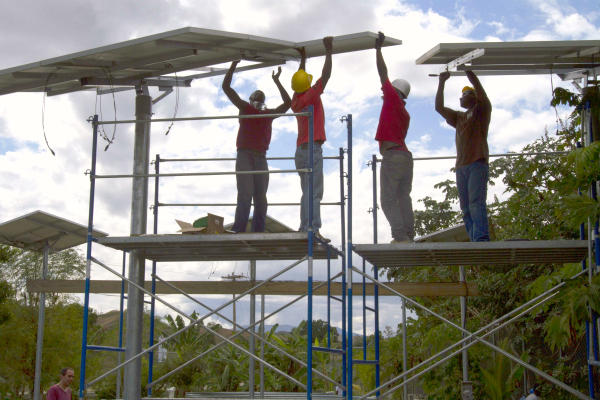 People install solar panels on the Saint-Michel health center and a fish hatchery in Boucan Carre, Haiti. The panels will provide the town with a dependable electricity supply for the first time. Only a quarter of Haiti's 10 million people has regular access to electricity. In 28 countries, Barefoot College is teaching people to harness solar power for electricity.  <P>Dieu Nalio Chery/AP/File