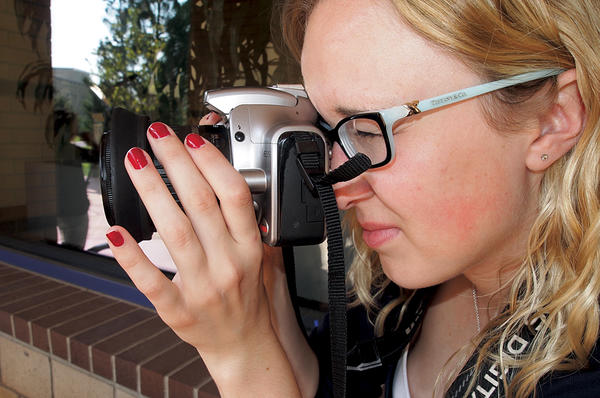 Dallas Jessup looks through a digital camera. The recent college graduate has already produced two films that teach basic self-defense.  <P>Just Yell Fire