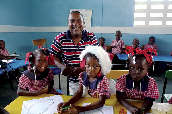 Tony Boursiquot stands with children at a Star of Hope school in Jeanton, Haiti, 60 miles north of Port-au-Prince. He was born in a village in southern Haiti, then went to live with relatives in the capital. He worked for an American woman who paid for his college in exchange for being her driver and houseboy.  <P>Gary G. Yerkey