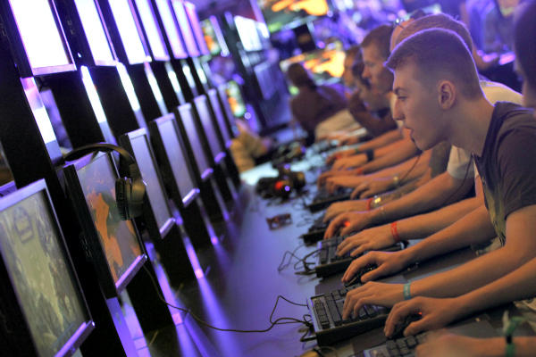 Visitors play World of Warcraft during the Gamescom 2011 fair in Cologne, Germany. By the time average Americans turn 21, they have played 10,000 hours of video games. Games for Change advocates using some of that time on games that result in social good.  <P>Ina Fassbender/Reuters/File