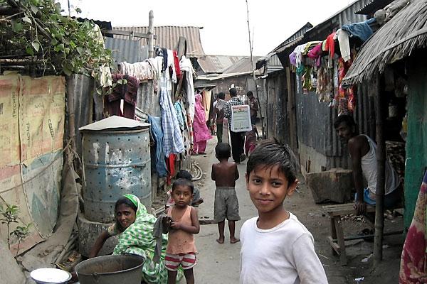 Residents of the Vasantek slum near Dhaka, Bangladesh, put food waste into large metal barrels.