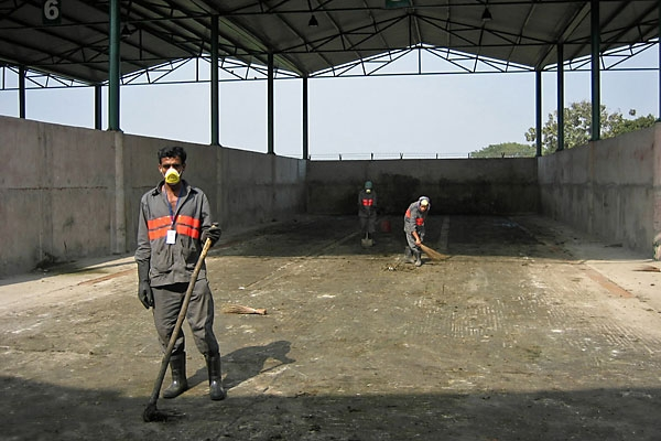 Workers at the Bulta CDM plant clean out a composting area for market waste.
