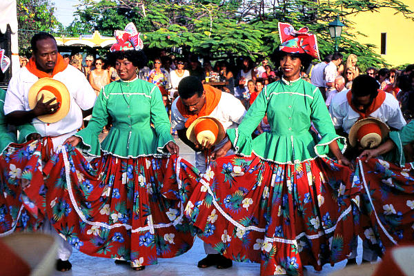 Costumed dancers perform a folk dance for tourists at a restored plantation in Curacao. The island nation in the southern Caribbean is considering using cold seawater drawn up from the ocean's depths to generate electricity.  <P>R. Norman Matheny/Staff/File