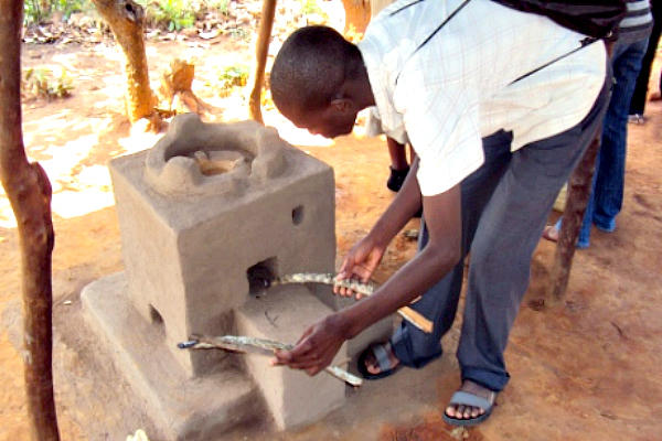 A young man demonstrates how to insert wood into an Esperanza cooking stove in Malawi's Rumphi North region. The locally produced stoves use less wood, saving forests and easing the lives of families.  <P>Karen Sanje/AlertNet