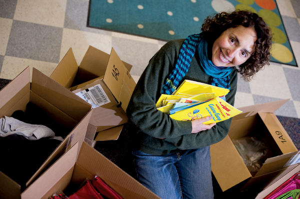 Pam Koner holds an armload of gently used books to be mailed to children in a less-advantaged town through her Giving Works! program.  <P>Ann Hermes/Staff