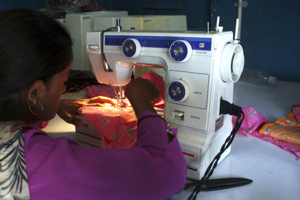 A woman sews clothes on a sewing machine driven by solar energy in Ahmedabad in western India. When night falls in remote parts of Africa and the Indian subcontinent, hundreds of millions of people without access to electricity turn to candles or flammable and polluting kerosene lamps for illumination. Solar power is becoming an economical way to bring light to these rural regions where a lack of electricity has stymied economic development, literacy rates, and health.  <P>Amit Dave/Reuters/File