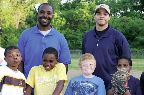 Cle Ross (back l., with Marquis Roby Sr., a KCK RBI league coach, and youth baseball players) was given sports equipment anonymously as a child and eventually played minor league baseball. Now he helps urban youths through Major League Baseball's Reviving Baseball in Inner Cities program.  David Conrads