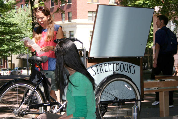 Laura Moulton (standing) pedals her bicycle-powered Street Books library to locations around Portland, Ore., providing books to the city's homeless, who don't qualify for library cards.  <P>Courtesy of Ben Parzybok