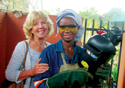 Libby Weir (l.) poses with Ntokozo Zulu, who is enrolled in a welding course that Ms. Weir is sponsoring. <P>David Canning