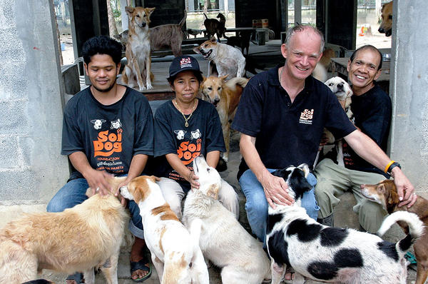 John Dalley (second from r.) relaxes with Soi Dog Foundation staffers and dogs rescued from Thailand's illegal dog meat trade. <P>Courtesy of John Dalley