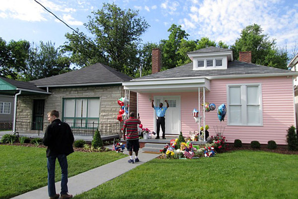 A law enforcement officer (on duty at the house) mugs for a visitor in front of Muhammad Ali's childhood home in Louisville, Ky. Photo - Ruth Walker