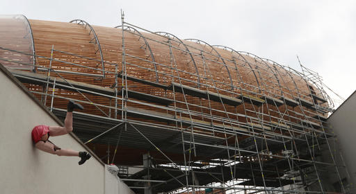 In this Monday, Sept. 19, 2016 photo a giant object resembling a zeppelin airship is being installed on the rooftop of an arts center in Prague, Czech Republic. The 42-meter long and 10-meter wide ship is planned to seat some 120 people on its cascade steps. It will be used for authors' reading and debates about literature to complement exhibitions at the DOX Centre for Contemporary Art, one of the most innovative and challenging galleries in the Czech capital. (AP Photo/Petr David Josek)