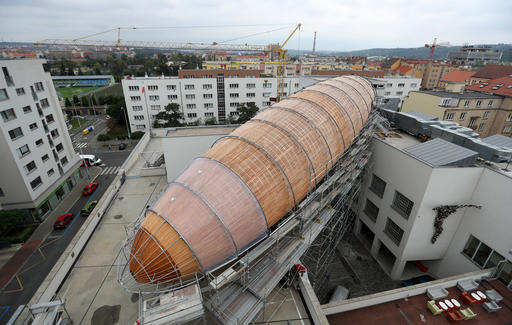 A giant object resembling a zeppelin airship is being installed on the rooftop of an arts center in Prague, Czech Republic, Monday, Sept. 19, 2016. The 42-meter long and 10-meter wide ship is planned to seat some 120 people on its cascade steps. It will be used for authors' reading and debates about literature to complement exhibitions at the DOX Centre for Contemporary Art, one of the most innovative and challenging galleries in the Czech capital. (AP Photo/Petr David Josek)