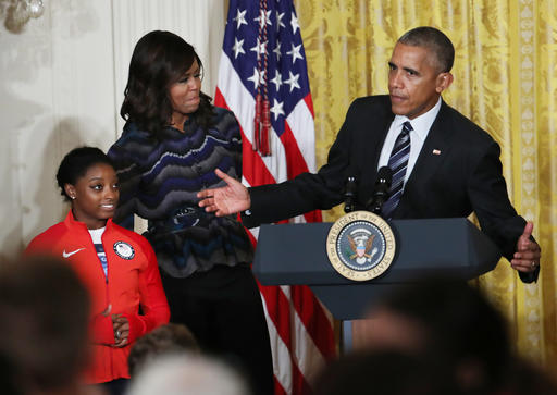 President Barack Obama, with first lady Michelle Obama and Olympic gold medal gymnast Simone Biles speaks in the East Room of the White House in Washington, Thursday, Sept. 29, 2016, after being presented with a surf board signed by the U.S. 2016 Olympians during a ceremony honoring the members of the 2016 United States Summer Olympic and Paralympic Teams. (AP Photo/Manuel Balce Ceneta)