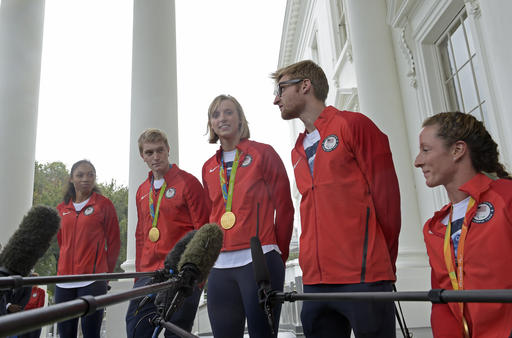 Olympic gold medal winner swimmer Katie Ledecky, center, accompanied by, from left, Olympic runner Allyson Felix, Olympic BMX rider Connor Fields, Paralympic Swimmer and Navy veteran Brad Snyder, and Paralympic wheelchair racer Tatyana McFadden, speaks outside the White House in Washington, Thursday, Sept. 29, 2016, following a ceremony where President Barack Obama honored the Olympics teams. (AP Photo/Susan Walsh)
