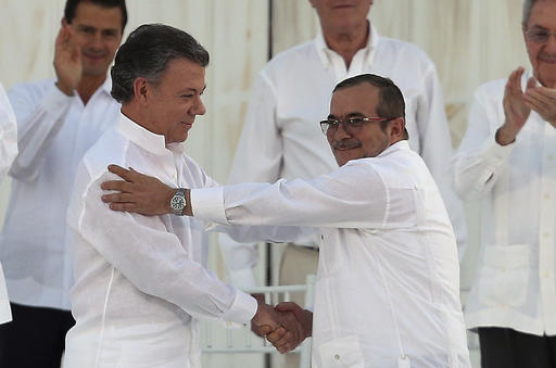 In this Monday, Sept. 26, 2016 file photo, Colombia's President Juan Manuel Santos, left, and the top commander of the Revolutionary Armed Forces of Colombia (FARC) Rodrigo Londono, known by the alias Timochenko, shake hands after signing a peace agreement between Colombia's government and the FARC to end over 50 years of conflict in Cartagena, Colombia. Santos won the Nobel Peace Prize Friday, Oct. 7, for his efforts to end a civil war that killed more than 200,000 Colombians. (AP Photo/Fernando Vergara, File)