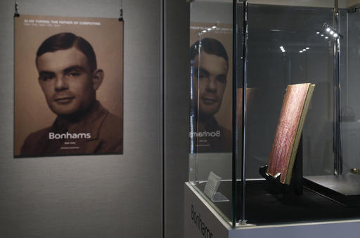 In this Thursday, March 19, 2015 file photo, a notebook of British mathematician and pioneer in computer science Alan Turing, the World War II code-breaking genius, is displayed in front of his portrait during an auction preview in Hong Kong. Britain's government will posthumously pardon thousands of gay and bisexual men convicted under long-repealed anti-gay laws. The calls for a more sweeping action came after World War II codebreaker Alan Turing was awarded a posthumous royal pardon in 2013 after a conviction of indecency in 1952. The gay computer science pioneer was stripped of his security clearance and later committed suicide. (AP Photo/Kin Cheung, File)